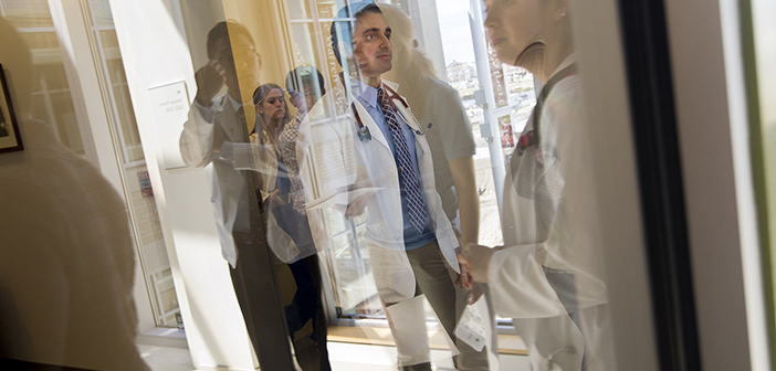 Anshul Parulkar '10 MD'18 walks to the case study room where students will examine a standardized patient with an opioid addiction.