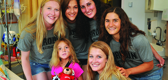 GOOD SPORTS: Members of the women's volleyball team visit a patient at Hasbro Children's Hospital last summer. Photo by Bill Murphy/Lifespan
