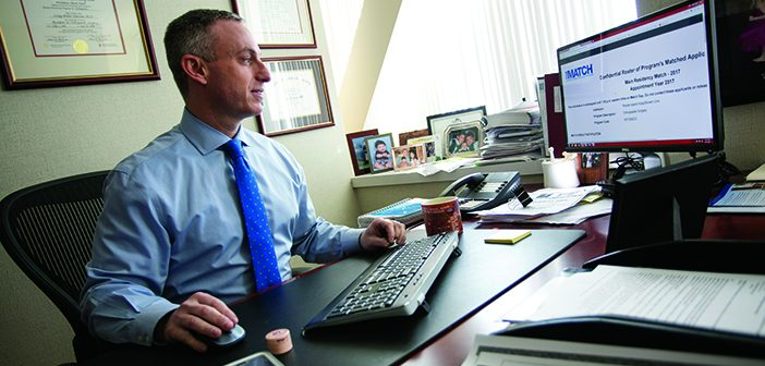 """PRIVATE PARTY: While med students celebrate with family and friends, Residency Program Director Craig Eberson emails the news to his orthopedics colleagues. """"It is exciting,"""" he says. Photo by Al Weems"""
