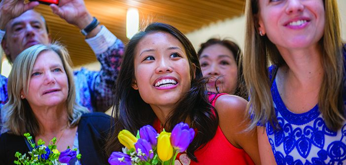 Christina Lam '13 MD'17 watches a slideshow of memories from her class. Photo by David DelPoio.