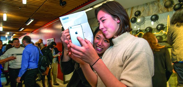 PROOF: Katie Pivarnik MD'17, right, snaps a photo of VyVy Trinh '11 MD'17's letter. Photo by David DelPoio