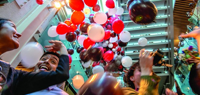 As the clock strikes noon, balloons fall and students tear their envelopes open. Photo by David DelPoio