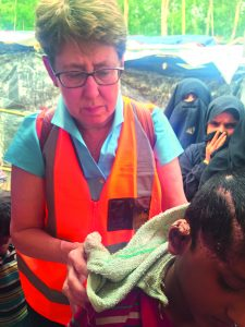 VIOLENT CONFLICT: Jane Carter treats a child with a gunshot wound in Bangladesh. Photo courtesy Ruhul Abid