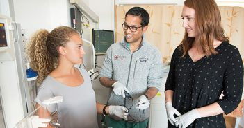 BRIDGING THE GAP: Neonatalogy fellow Ravi D'Cruz (center) works with biomedical engineering students Kabisa Baughen (left) and Shannon Crowley in the NICU. Photo by Webb Chappell.