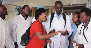 TECH SAVVY: Grace Wanjiku (in red shirt) demonstrates a smartphone-connected, portable ultrasound to ICU physicians at Kenyatta National Hospital in Nairobi in April. Photo by Shirley Wu, MD.